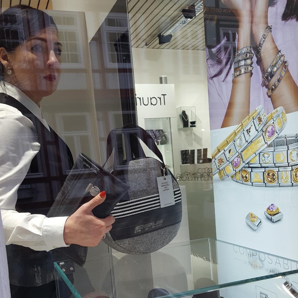 Godje Mahn posiert mit zwei Taschen im Schaufenster