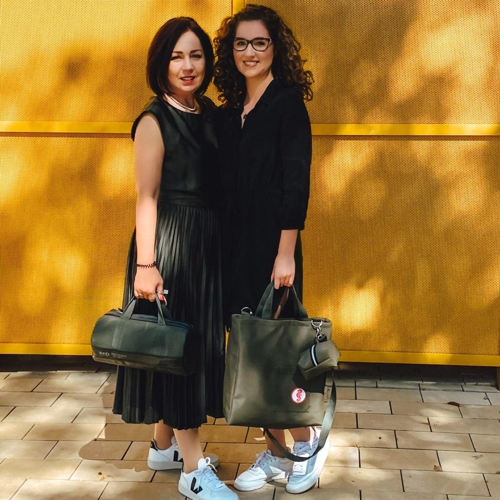 Godje und Pauline Mahn posieren gemeinsam mit Khaki Taschen vor einer gelben Wand